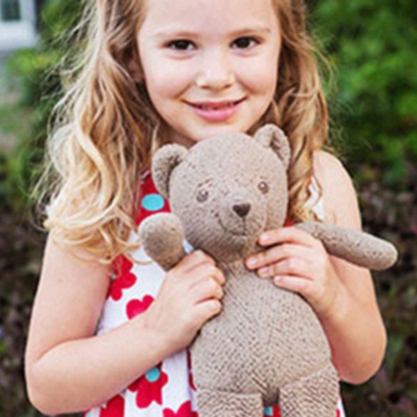 Young girl moving holding stuffed bear