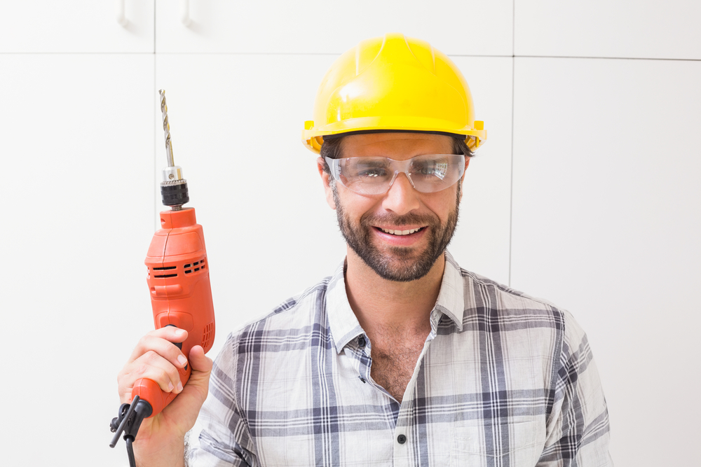 Construction worker holding power drill in a new house