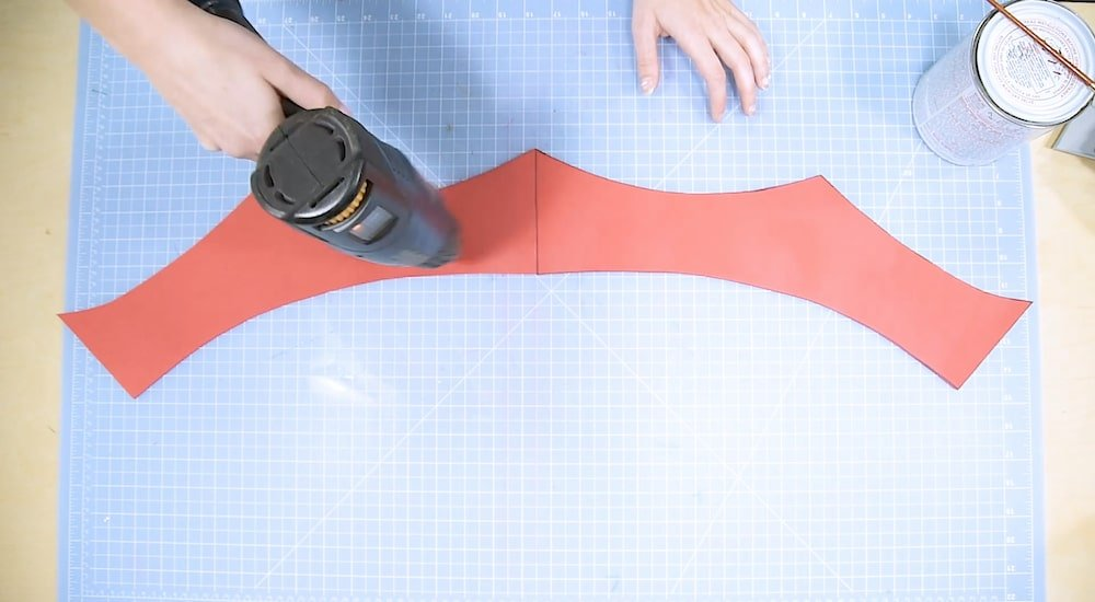 Cosplayer applying heat to EVA foam using a heat gun