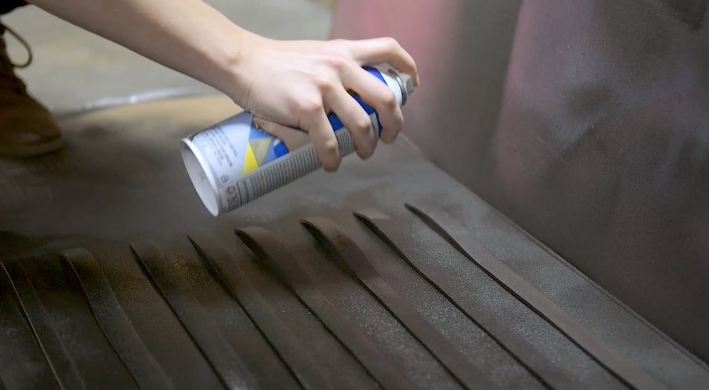 Cosplayer spraying foam strips with a can of black Plasti Dip