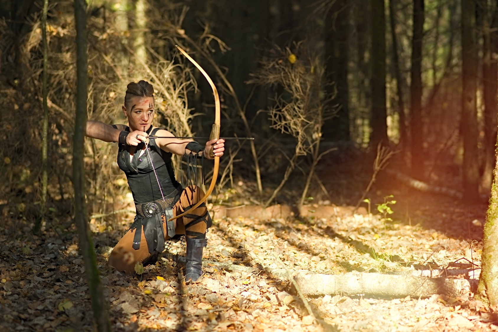 Archer cosplay posing in the woods with a wooden bow and arrow