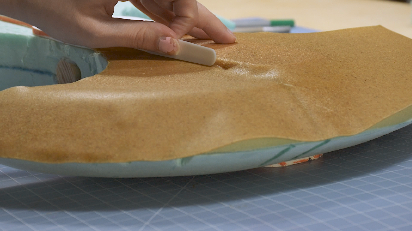 Cosplay maker pressing thermoplastic Worbla onto a foam cosplay weapon