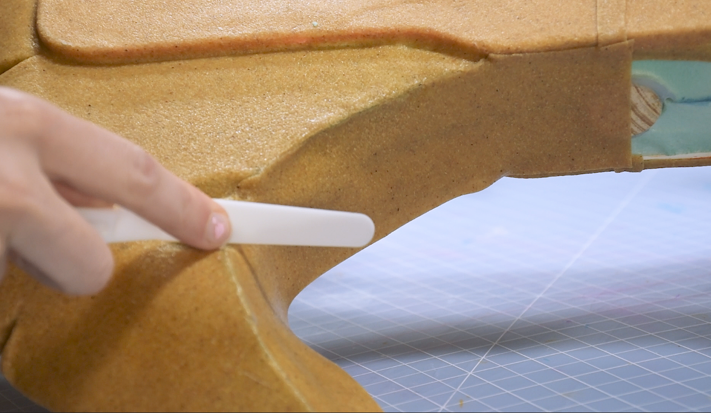 Cosplay maker pressing down Worbla thermoplastic to the shape of a foam cosplay axe weapon using a clay tool