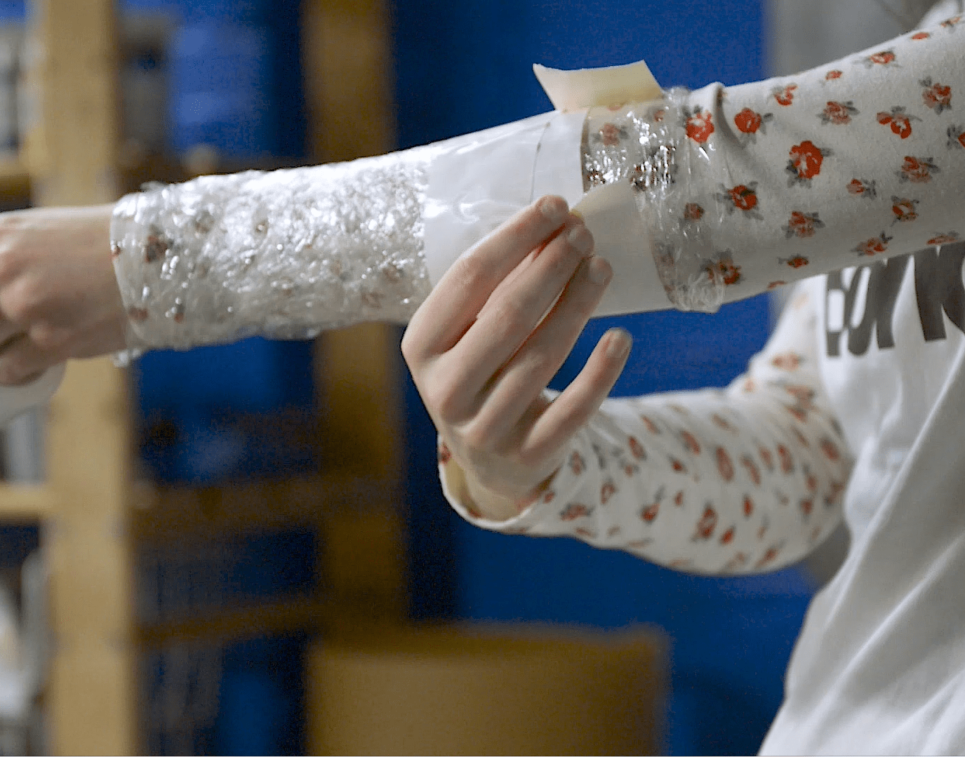 Cosplayer wrapping tape around plastic wrap for armor pattern