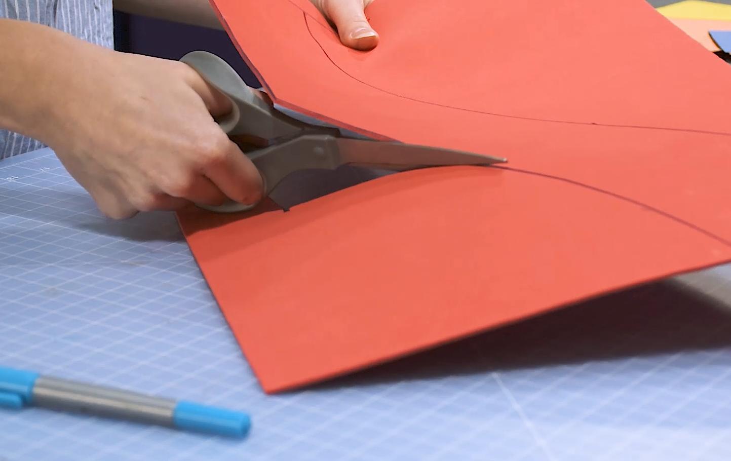 Cosplayer cutting a piece of craft EVA foam with scissors