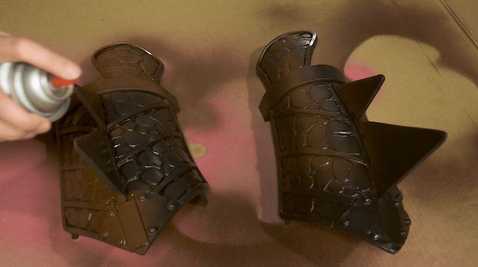 Cosplay armor wrist guards being spray painted brown base coat