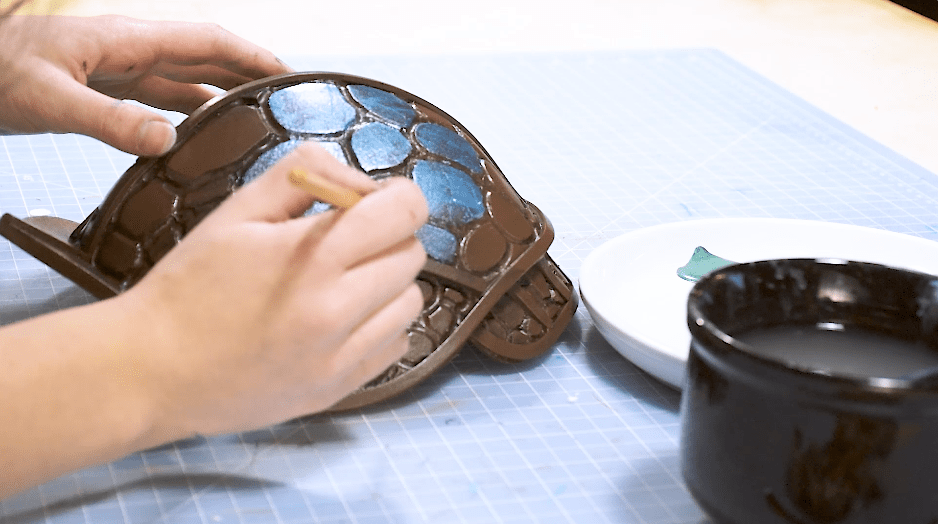 Cosplayer layering acrylic paints on top of spray paint for professional armor finishh