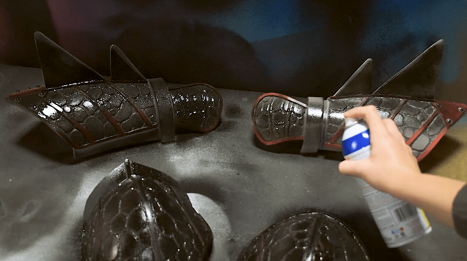 Cosplay foam armor pieces being sealed with rubberized paint from a spray can
