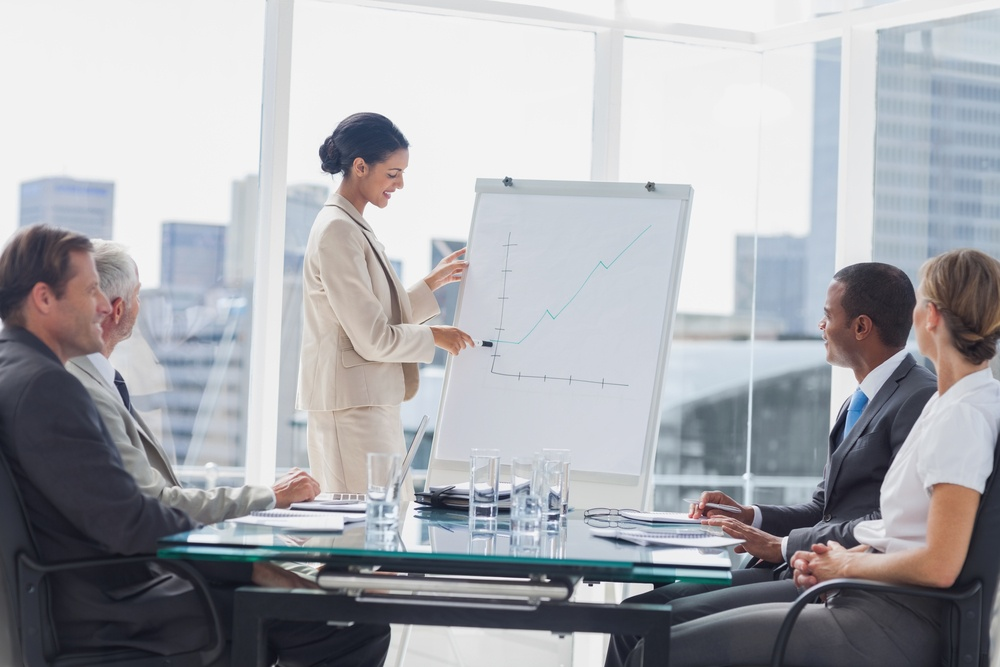 Businesswoman pointing at a growing chart during a meeting in the meeting room.jpeg