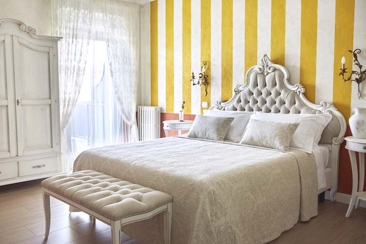 mustard and white strippeed wall with bed in front