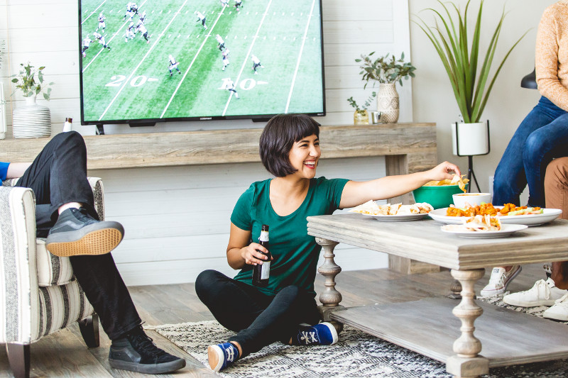 Friends watching football game and eating in manufactured home living room.