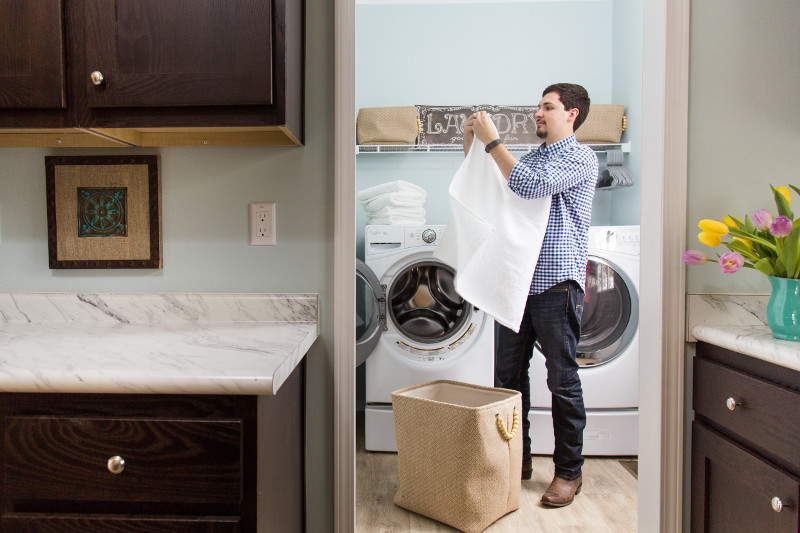 Man folding laundry in a manufactured home laundry room.