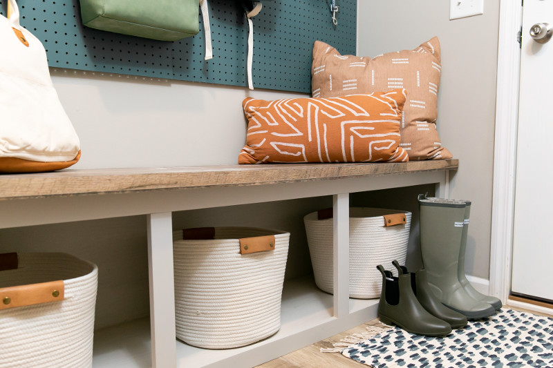 Manufactured home entry way with bench seating, baskets, shoe storage, and throw pillows.