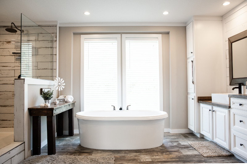 Master bathroom with separate shower and tub and white cabinetry.