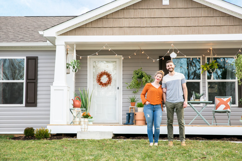 Young couple standing in front of their modular home with gorgeous front porch and garden.