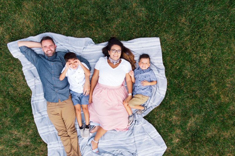Family laying on a blanket in the grass in their yard during the summer