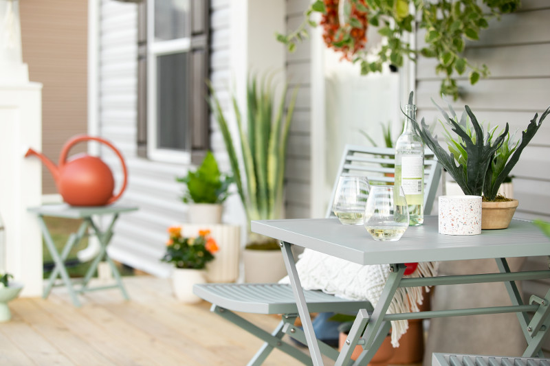 Manufactured home front porch with spring flowers, herbs and plants