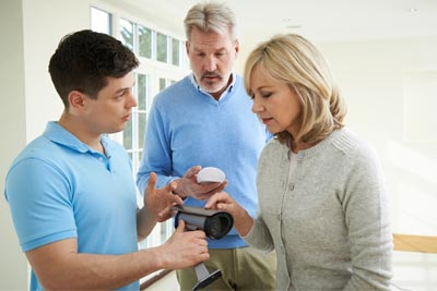 technician explaining home security camera system to couple