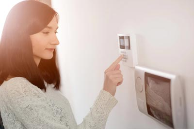 woman arming security system and viewing outdoor security  cameras