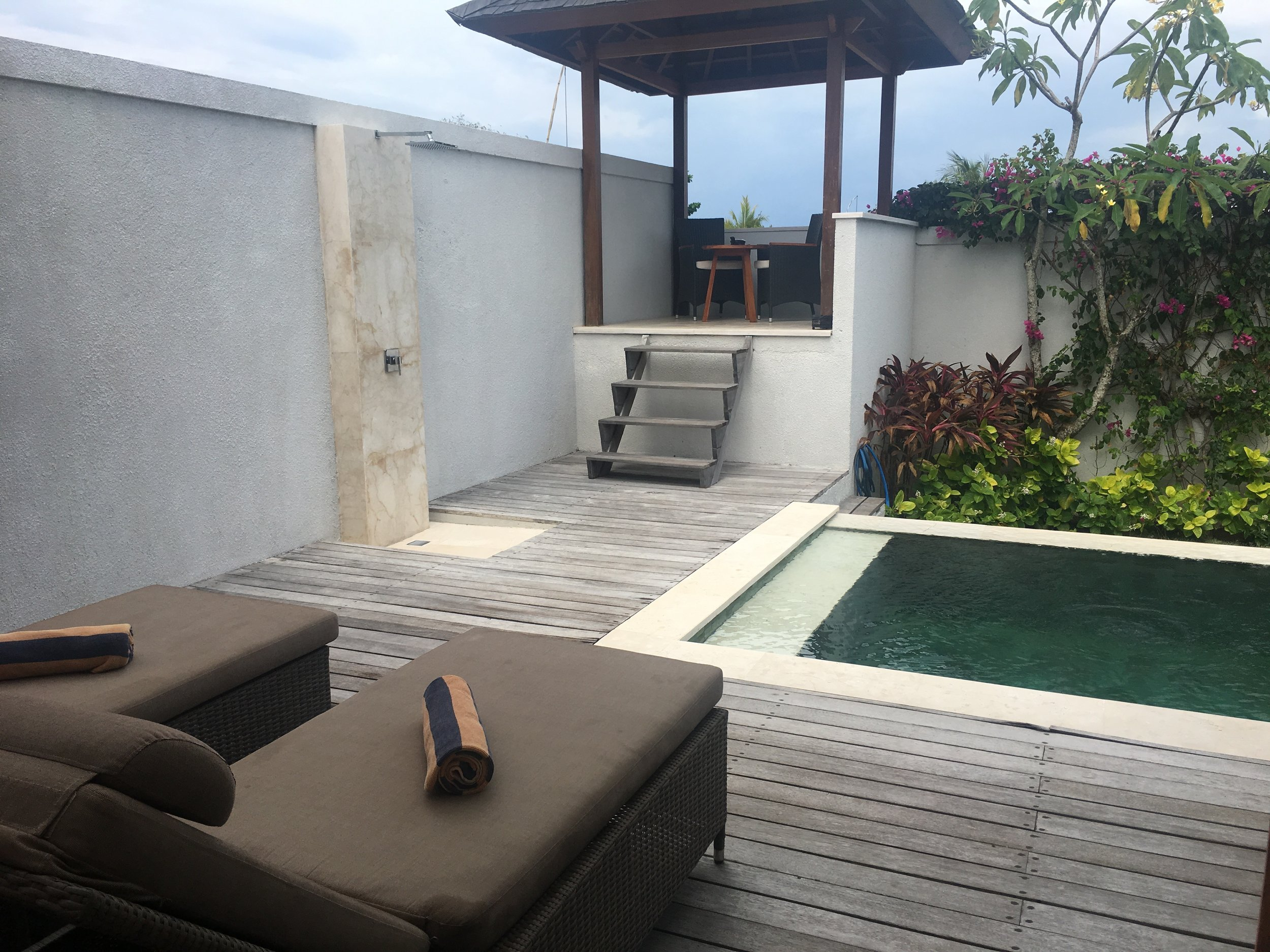 Sun loungers by the pool, an outdoor shower and a sea view from the shaded seating area