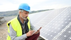 Mature engineer on building roof checking solar panels-184684-edited.jpeg