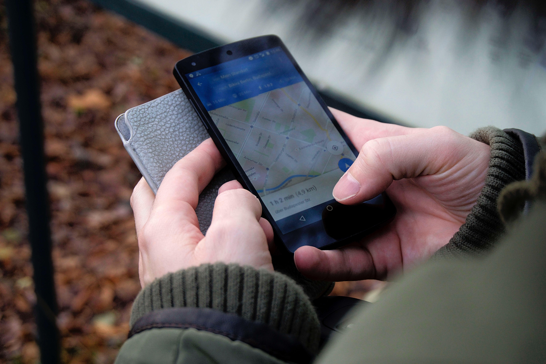 Persoon met smartphone navigeren via Google