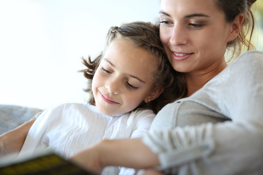 Mom%20with%20little%20girl%20reading%20book%20in%20sofa min