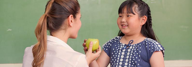 professora oferecendo uma maçã à aluna