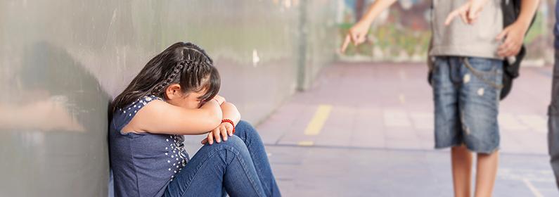 menina sentada no chão chateada enquanto dois meninos apontam para ela