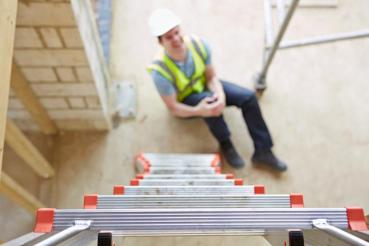 Worker holding leg at bottom of ladder